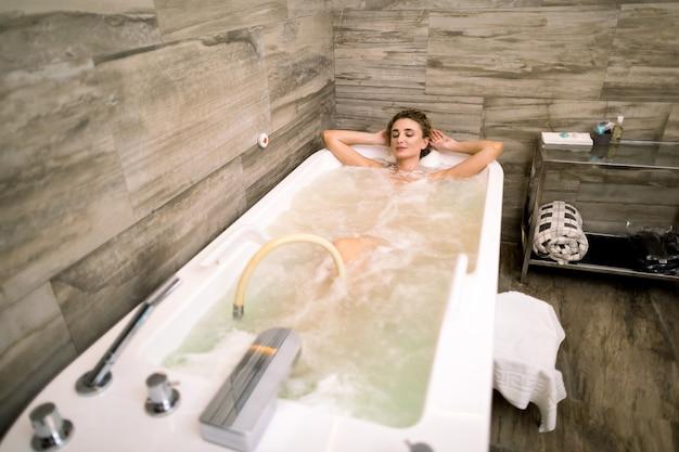 頭の後ろに手を繋いでいるハイドロマッサージ風呂でリラックスした幸せな白人の若い女性