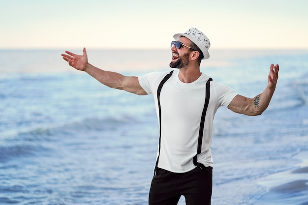Happy celebrating bearded man in hat and sunglasses posing with hands up at the resort on the sea