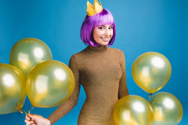 Happy celebrating moments of smiled young woman having fun with golden balloons . luxury fashionable dress, cut purple hair, crown, celebration, new year party, birthday.