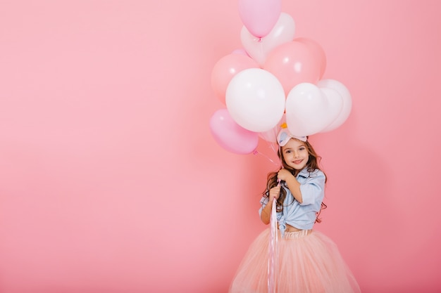 Happy celebration of birthday party with flying balloons of charming cute little girl in tulle skirt smiling to camera isolated on pink background. charming smile, expressing happiness. place for text