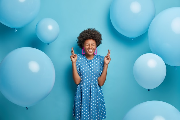Happy celebration concept. positive hopeful birthday girl crosses fingers, makes wish, believes all her dreams come true dressed in polka dot dress in one tone of wall. inflated balloons around