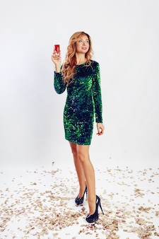 Happy celebration woman in green sequin  dress drinking wine, enjoying party. golden confetti.