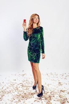 緑のスパンコールのドレスでワインを飲み、パーティーを楽しんで幸せなお祝いの女性。黄金の紙吹雪。