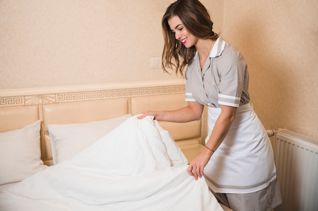 Happy chambermaid changing the bed sheet in the hotel room