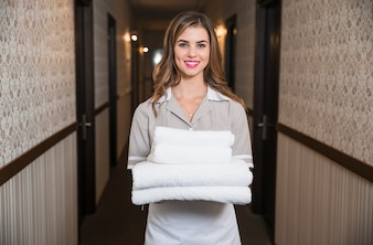 Happy chambermaid standing in the hotel corridor holding washed towels