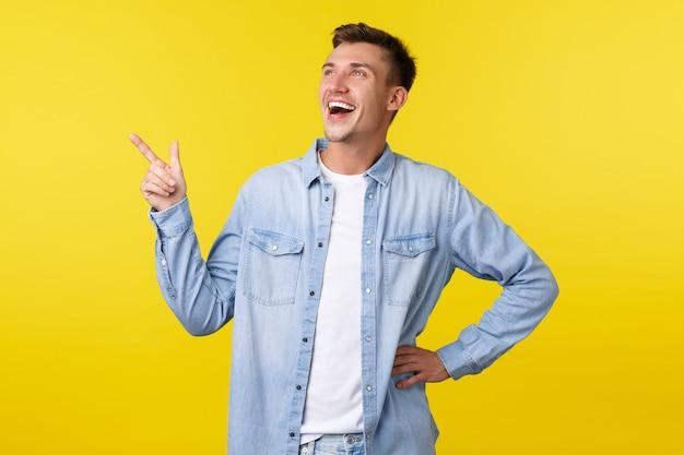 幸せなカリスマ的な金髪の男が左上隅を指して、面白いプロモーションバナーを笑い、素晴らしいイベントを楽しんで、楽しんで、黄色の背景の上に立っています。