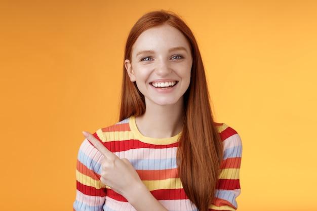 Счастливая харизматичная улыбающаяся молодая рыжая девушка, голубые глаза, искренняя нежная ухмылка, широко смеющаяся, весело обсуждает веселый концерт, указывая в верхнем левом углу, показывая потрясающий продукт, оранжевый фон