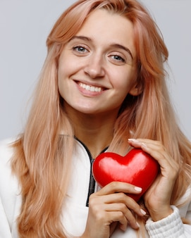 Happy charity volunteer woman with holding red heart, looking