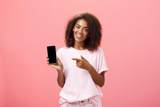Smarpthoneを保持し、デバイス画面を指してスタイリッシュな衣装で幸せな魅力的なアフリカ系アメリカ人の女性。