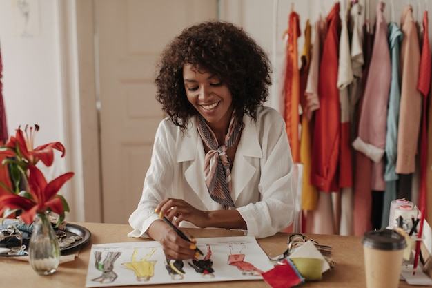 トレンディな白いブラウスとシルクのスカーフの笑顔とオフィスで新しいファッションの服をデザインする幸せな魅力的なブルネットの巻き毛の女性