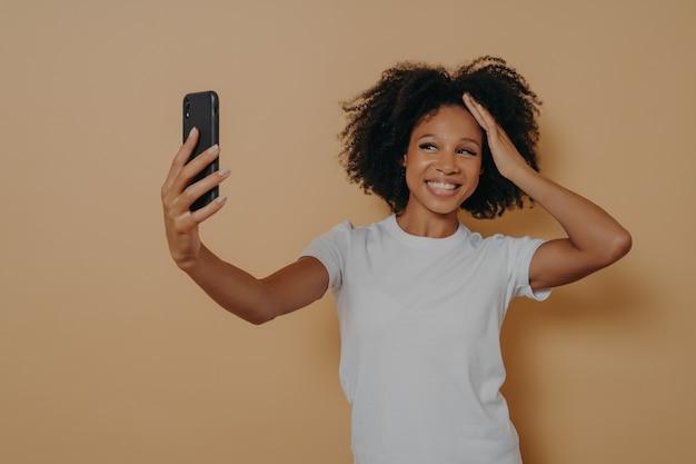 ベージュの壁に隔離された、現代のスマートフォンで写真のセルフィーを作り、陽気に笑っている白いtシャツの幸せな魅力的な暗い肌の女性20代。携帯電話で写真を撮るポジティブな若いアフリカの女性
