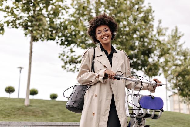 행복하고 매력적인 검은 피부의 여성이 야외에서 자전거와 함께 포즈를 취합니다.