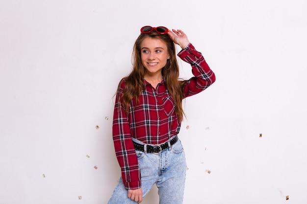 離れて見て、笑顔の孤立した壁の上にポーズをとって赤い眼鏡でシャツとジーンズを着て幸せな魅力的な女の子