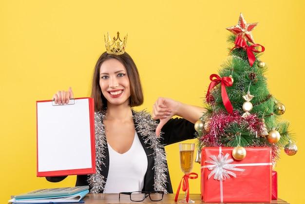 사무실에서 부정적인 제스처를 만드는 문서를 들고 왕관과 함께 소송에서 행복 매력적인 아가씨