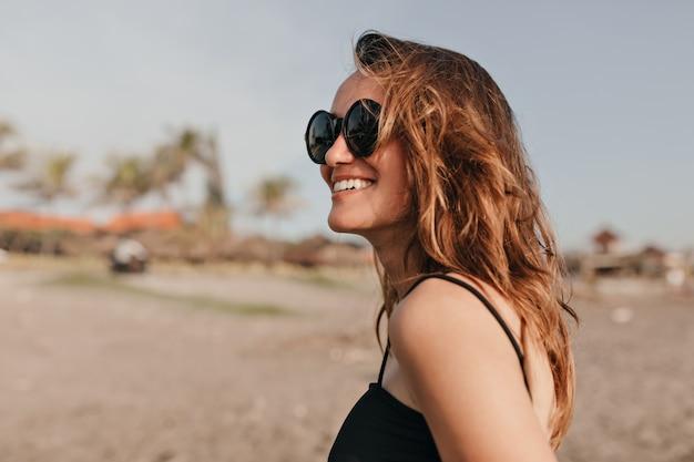 Счастливая очаровательная улыбающаяся женщина с темными волнистыми волосами гуляет на солнце на пляже и наслаждается отпуском на берегу океана