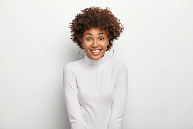 아프로 헤어 스타일을 가진 행복한 매력적인 여자, 백설 공주 폴로 넥 점퍼를 입고 쇼핑을 한 후 기분이 좋습니다.