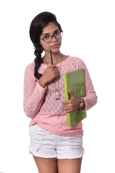 Happy charming young girl standing and holding notebook and thinking
