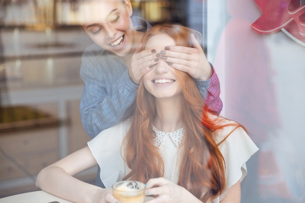Happy charming young woman covered eyes to her female friend in cafe
