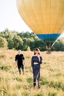 Happy charming young woman in fashionable black clothes, standing in beautiful summer green field, while her boyfriend is walking to her