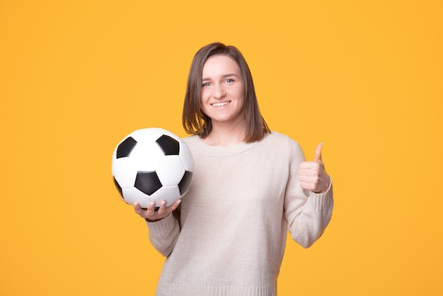 Happy charming young woman holding soccer ball and showing thumb up gesture