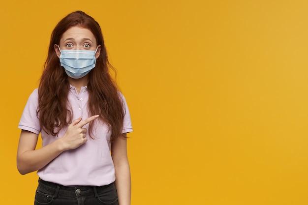 黄色の壁に隔離されたコピースペースで立って指で横を指して立っている医療保護マスクを身に着けている幸せな魅力的な若い女性