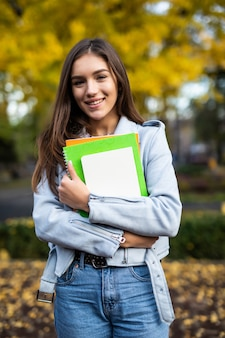 Happy charming young woman with backpack standing and holding notebooks in park