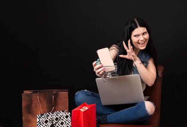 Счастливая очаровательная молодая женщина с тележкой для покупок и смартфоном, использующая ноутбук для покупок в интернете