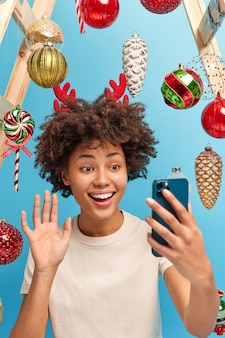 Happy cheerful african american woman waves hand at smartphone screen calls relatives stays at home during christmas time enjoys cozy atmosphere decorates room before winter holidays. festive mood