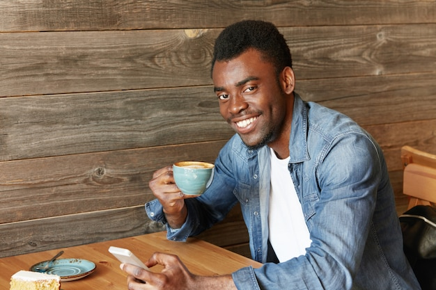 Happy cheerful african student holding mug, drinking fresh cappuccino, browsing internet and checking newsfeed on social media, using cell phone during coffee break at modern cafe with wooden walls
