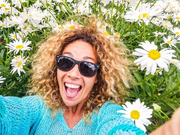 幸せな陽気で美しい大人の白人女性は、春と楽しい人々のコンセプトのためにデイジーの花の牧草地に横たわる自然をお楽しみください