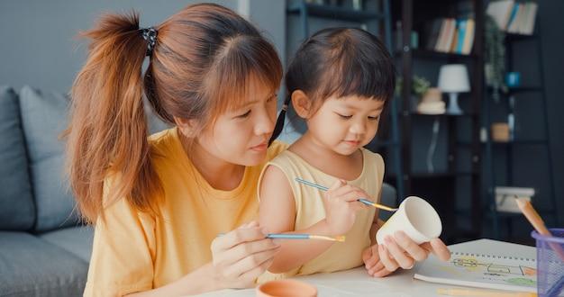 幸せな陽気なアジアの家族のお母さんは、家のリビングルームのテーブルでリラックスして楽しんでいる幼児の女の子のペイントセラミックポットを教えています