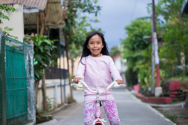 Happy cheerful asian child girl riding a bicycle