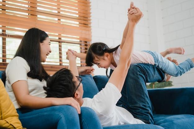 幸せな陽気なアジアの家族のお父さん、お母さんと娘が楽しんでいます