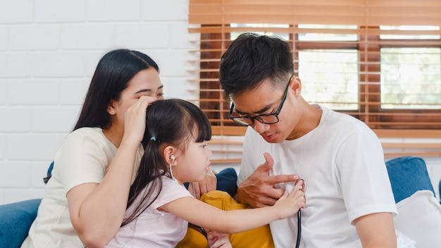 Happy cheerful asian family dad, mom and daughter playing funny game as doctor having fun on sofa at home
