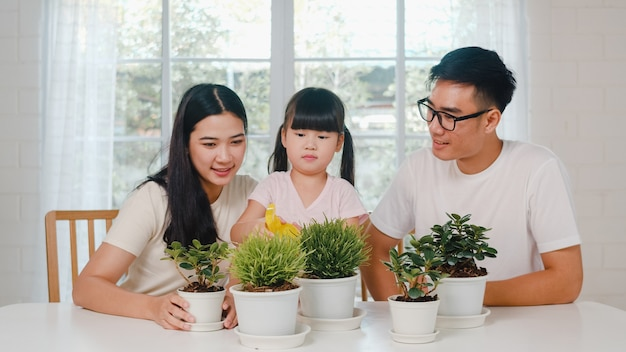 Happy cheerful asian family dad, mom and daughter watering plant in gardening near window at house