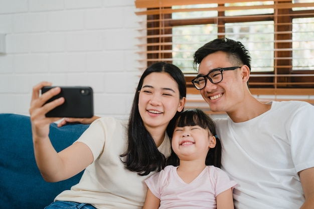 Happy cheerful asian family dad, mom and kids having fun and using smart phone video call on sofa at house.