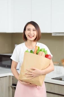 신선한 제품, 야채, 채소, 바게트, 바나나로 가득 찬 종이 가방을 들고 행복하고 쾌활한 아시아 여성.