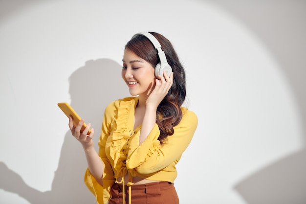 Happy cheerful asian woman wearing wireless headphones