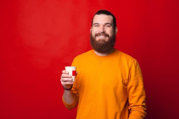 Счастливый веселый бородатый хипстер мужчина пьет чашку кофе над красным