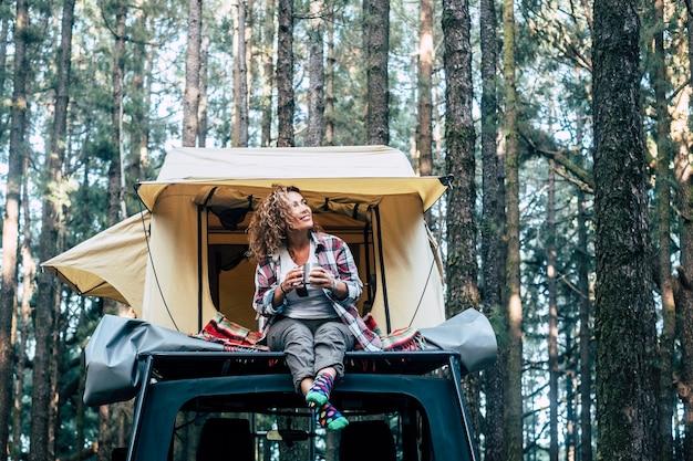 幸せな陽気な美しい人々の白人の大人の女性が、テントと森の周りにある車の屋根に座る