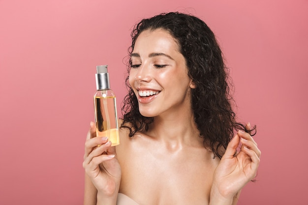 Happy cheerful beautiful young woman posing isolated over pink wall take care of her hair holding oil.