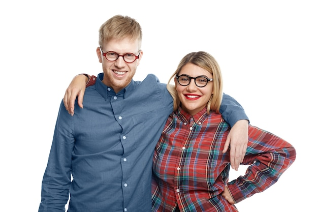 幸せな陽気な親友の男性と女性は、スタイリッシュな楕円形のアイウェアを身に着けて、長い分離の後に写真のポーズをとっている間、広く抱きしめ、笑顔で、ついにお互いを見てうれしいです