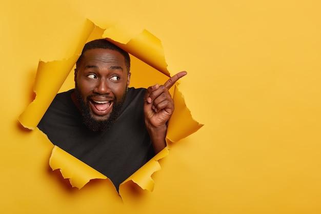 Счастливый веселый черный мужчина модель указывает указательным пальцем в сторону, держит рот открытым, показывает язык, привлекает ваше внимание к пустому пространству