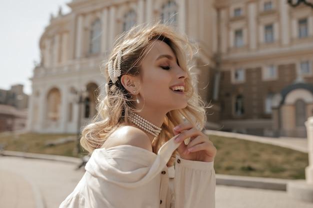 真珠のネックレスと白いブラウスで幸せな陽気なブロンドの巻き毛の女の子は広く笑顔で市内中心部を歩きます