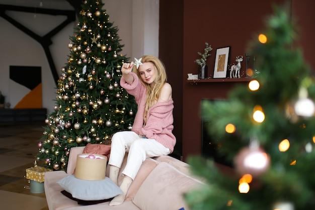 Счастливая веселая блондинка позирует у елки
