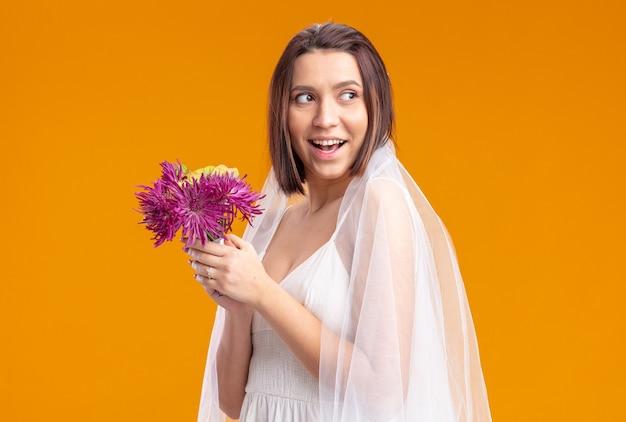 Sposa felice e allegra in un bellissimo abito da sposa che va a lanciare un bouquet di fiori da sposa sorridendo fiducioso in piedi sul muro arancione