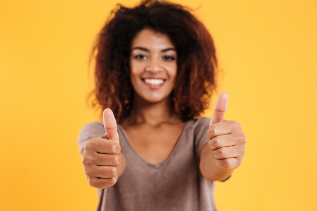 Happy cheerful brunette woman showing thumb up and smiling isolated
