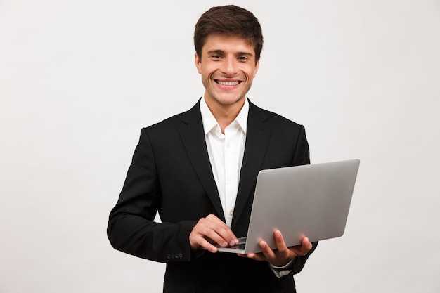 Happy cheerful businessman standing isolated holding laptop computer.