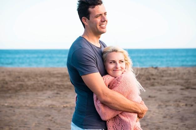 행복 명랑 백인 부부 포옹과 야외 여가 활동의 해변에서 사랑-우정과 젊은 좋은 사람들 사이의 관계-휴가와 즐기는 라이프 스타일 개념