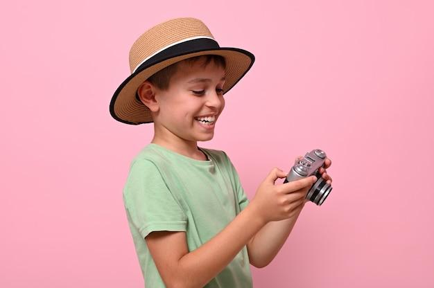 복고풍 빈티지 카메라를 들고 여름 옷을 입은 행복한 쾌활한 아이